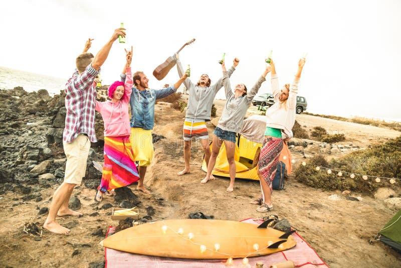 嬉皮朋友获得乐趣一起在海滩野营的音乐党 库存图片