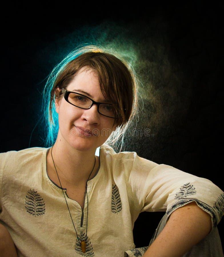 嬉皮礼服的年轻白种人妇女有蓝色和绿色头发的在黑背景点燃 库存照片