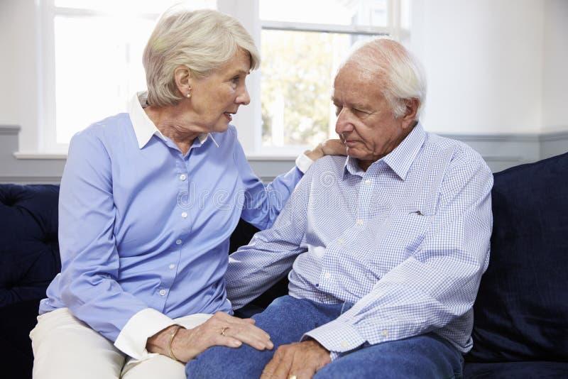 妻子在家谈话与沮丧的资深丈夫 免版税库存图片