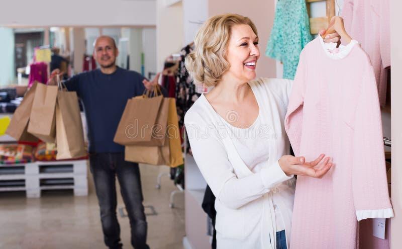 妻子在服装店,人的购买礼服不耐烦 库存照片