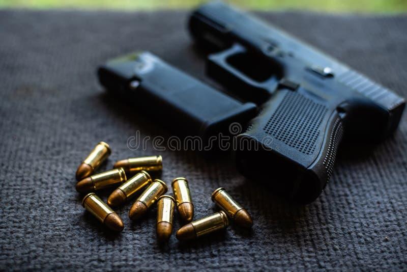 子弹和枪在黑天鹅绒书桌上 免版税库存照片