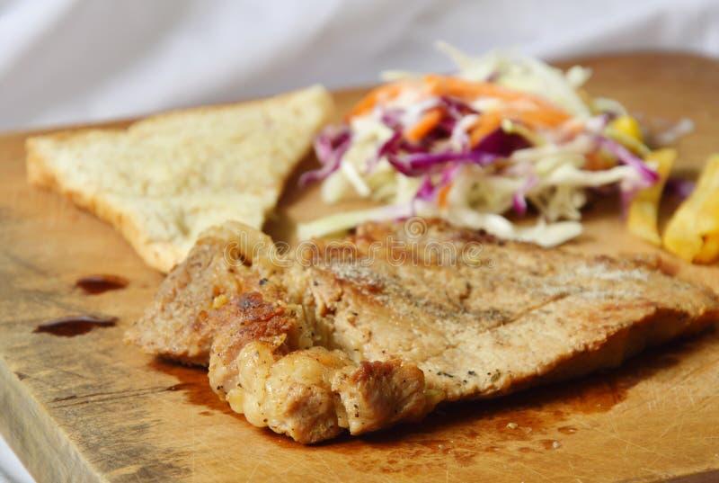 以子弹密击与法语油煎的和沙拉的猪肉牛排在剁块 免版税库存图片