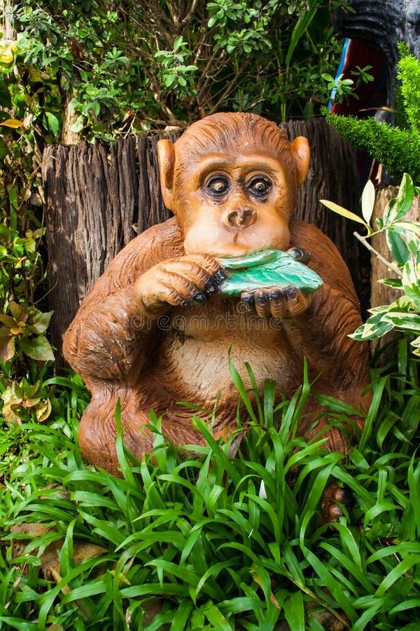 猴子雕象在庭院里 免版税库存照片