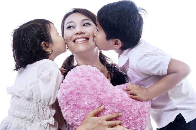 子项亲吻的愉快的母亲-查出 免版税库存图片