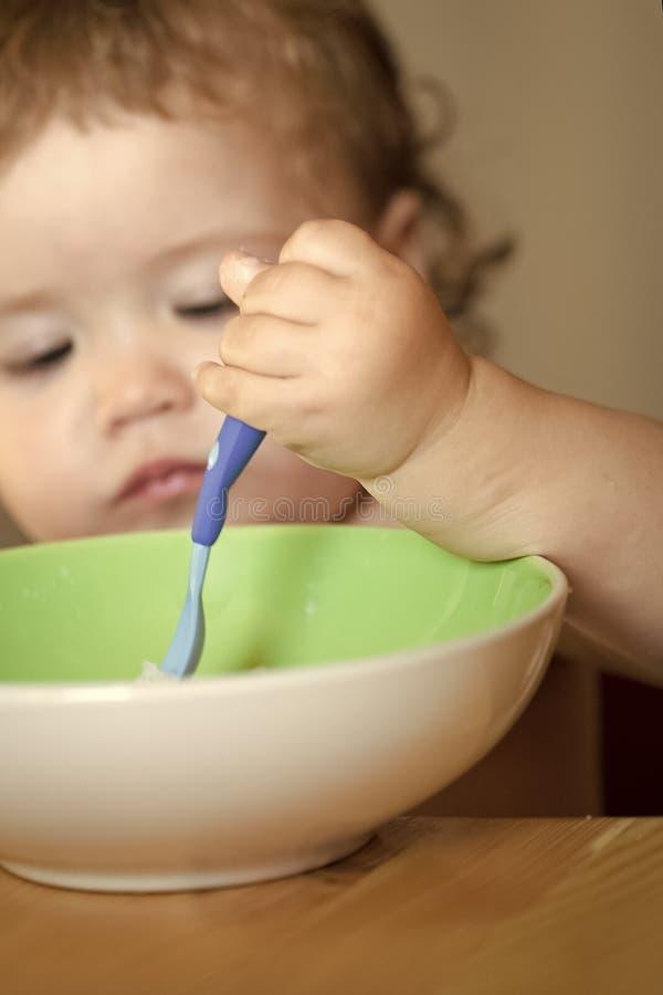 子项吃粥 画象白肤金发男孩吃 库存照片