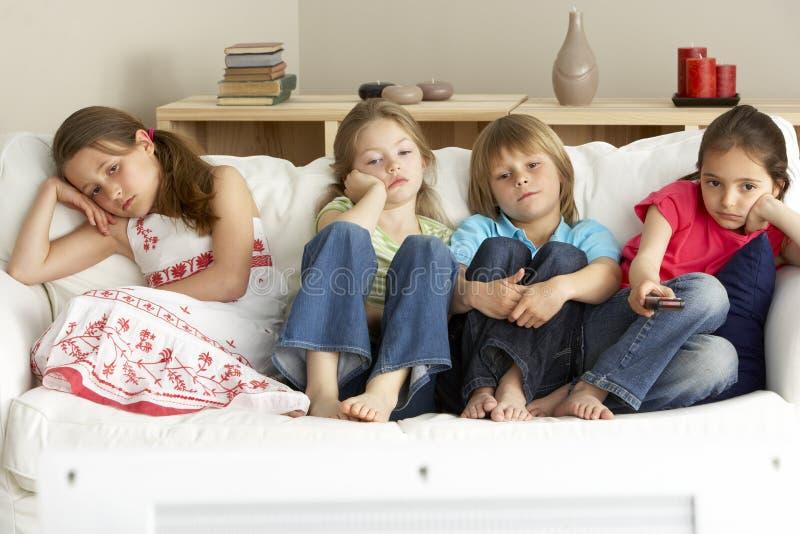 子项回家电视注意的年轻人 免版税库存图片