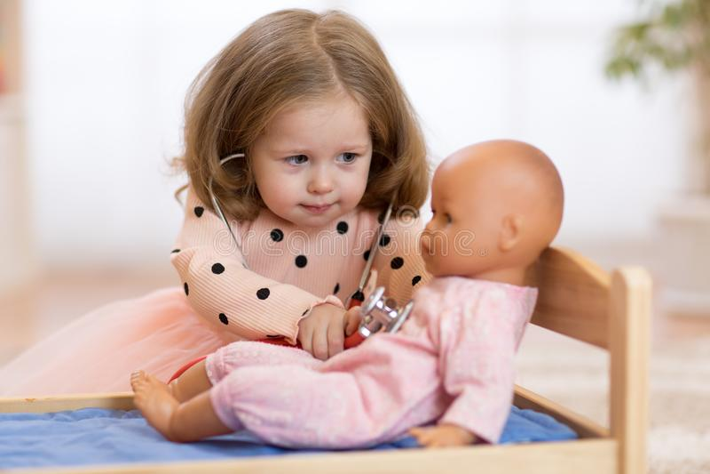 子项在幼稚园 孩子在托儿所 扮演有玩偶的小女孩学龄前儿童医生 图库摄影