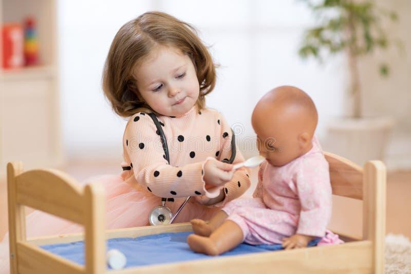 子项在幼稚园 孩子在托儿所 扮演有玩偶的小女孩学龄前儿童医生 库存照片