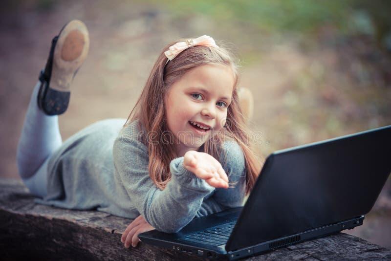 子项在有膝上型计算机的秋天公园 图库摄影