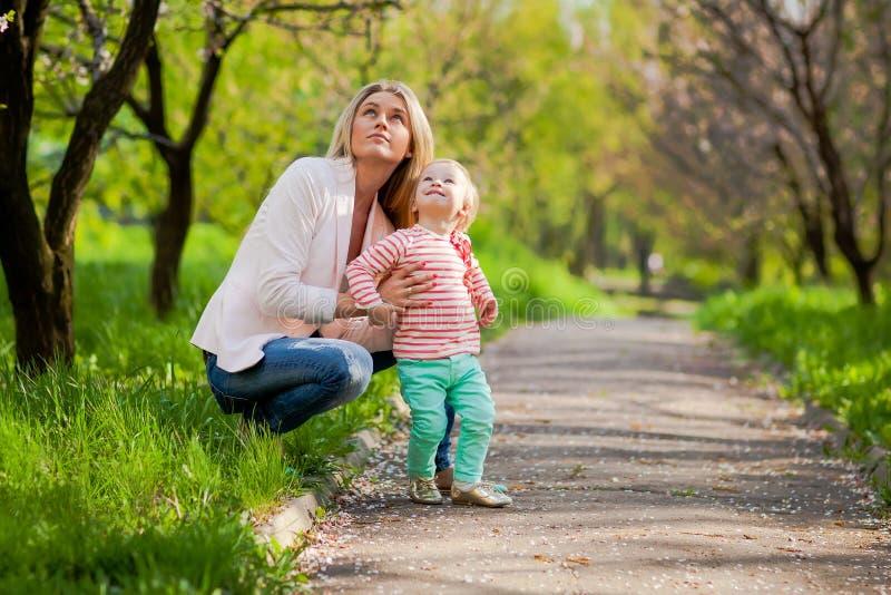 子项她的母亲公园春天 免版税库存图片