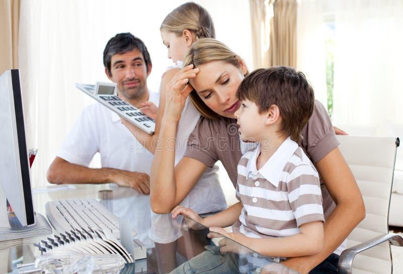 子项执行他们帮助的家庭作业的父项 免版税库存图片