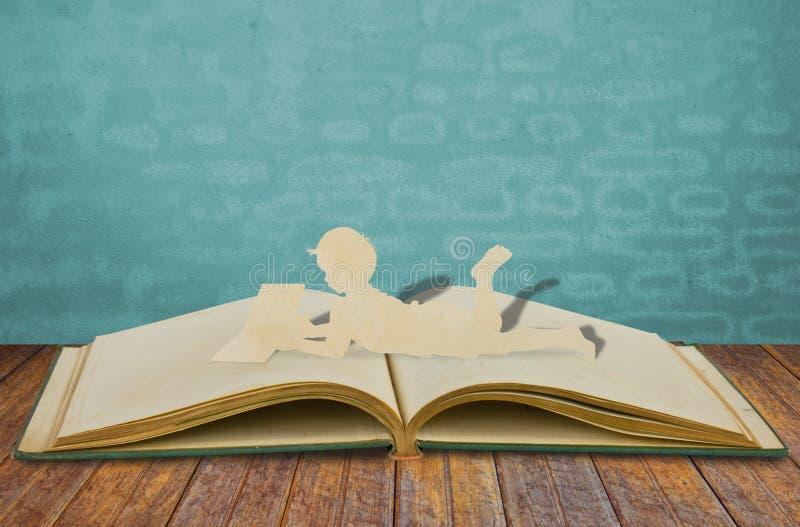 子项纸张剪切读了一本书 免版税库存照片