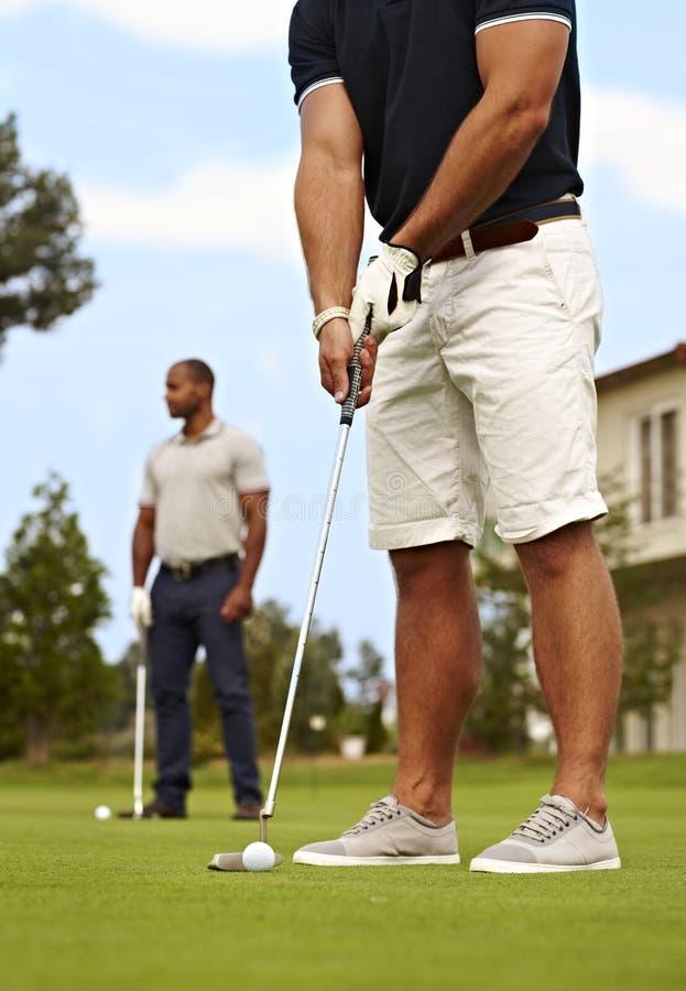 钻孔在绿色的高尔夫球运动员 库存图片