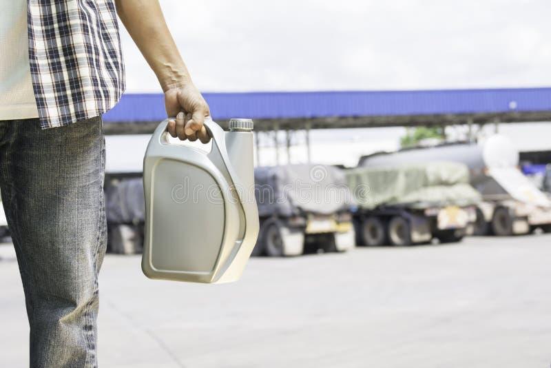 钻孔机油的灰色塑料罐在气体st的男性的手 库存照片