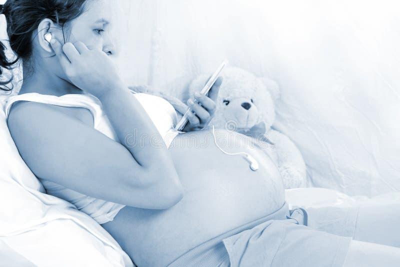 孕妇听到音乐为胚胎发育 免版税库存图片
