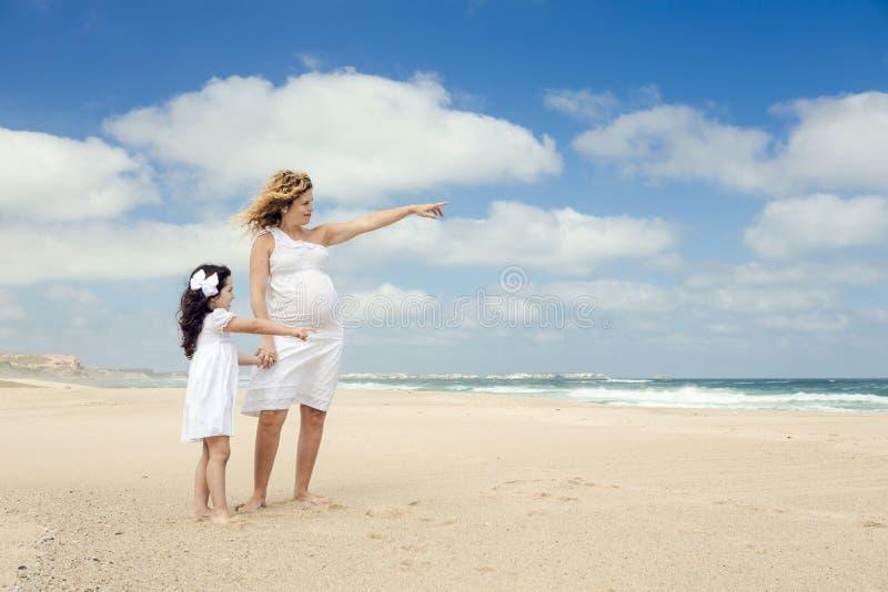 孕妇和她的女儿海滩的 免版税图库摄影
