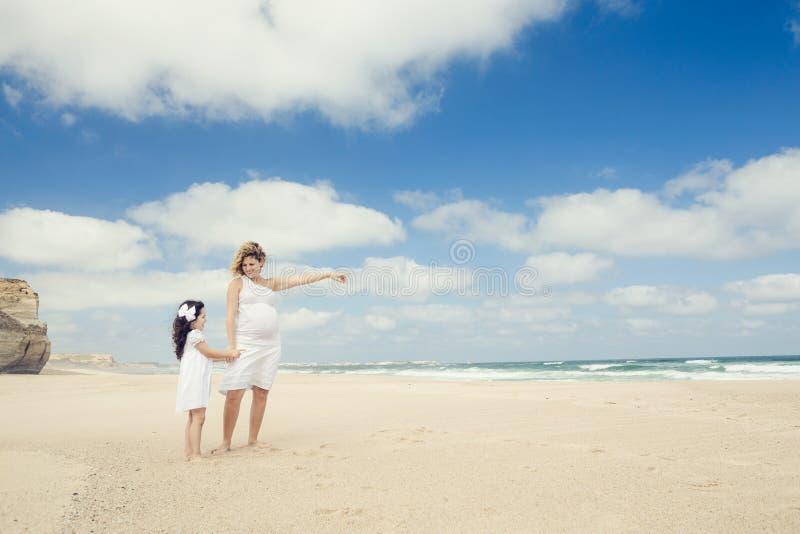 孕妇和她的女儿海滩的 库存照片