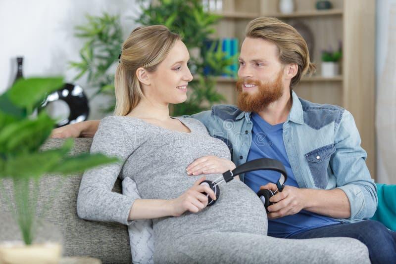 孕妇和英俊丈夫让婴儿听音乐 免版税图库摄影
