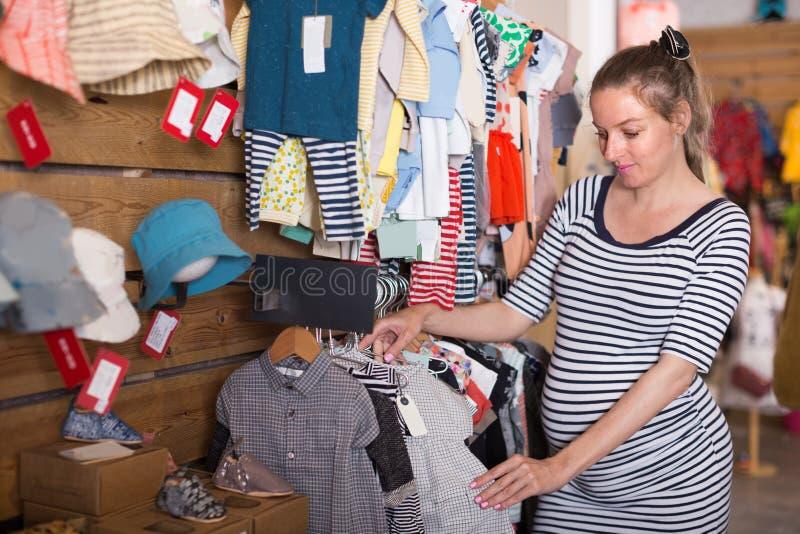孕妇在商店选择未来孩子的衣裳 免版税库存照片