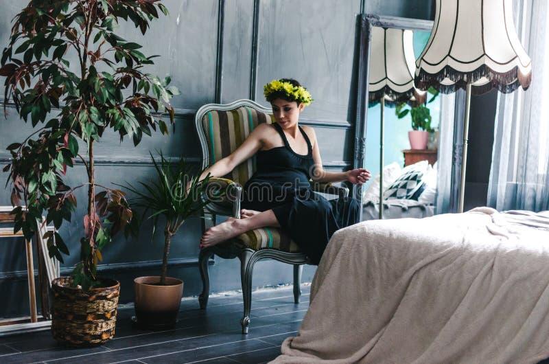 孕妇在扶手椅子坐由窗口在树旁边 她周道地看她的腹部 免版税库存图片
