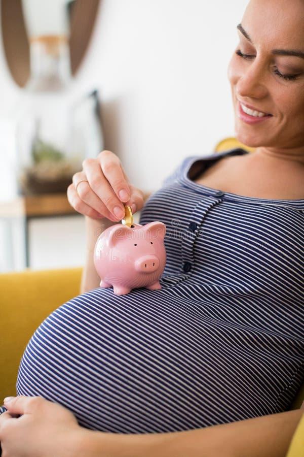 孕妇在放金钱的托儿所入存钱罐休息 免版税库存图片