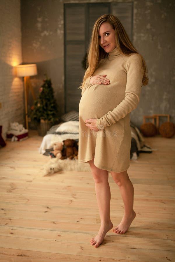 孕妇在腹部附近站立并且支持她的手 免版税库存照片