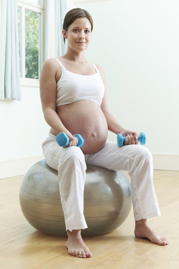 孕妇坐与重量的锻炼球 图库摄影