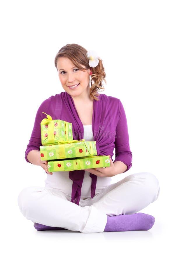 孕妇坐并且拿着有礼品的配件箱 免版税图库摄影