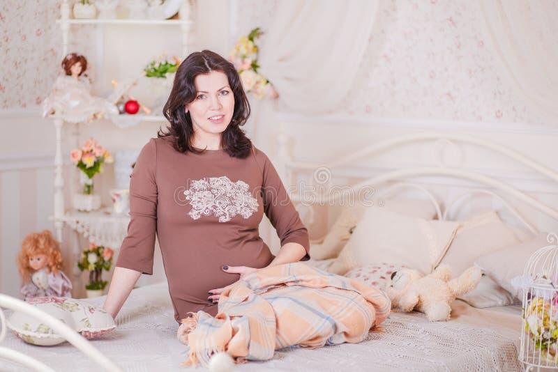 孕妇坐床 库存照片