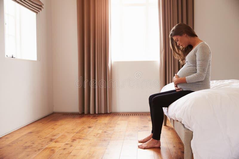 孕妇坐握腹部的床 库存图片