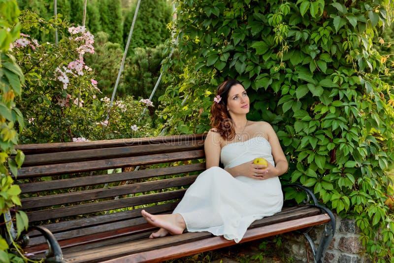 孕妇坐长凳温暖的天气 免版税库存照片