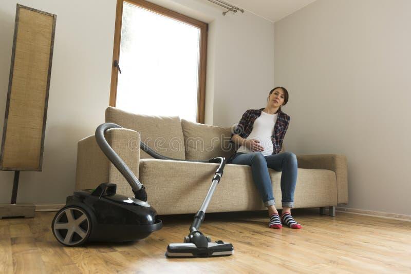 孕妇坐长沙发疲倦了于吸尘 家庭和大扫除概念 库存图片