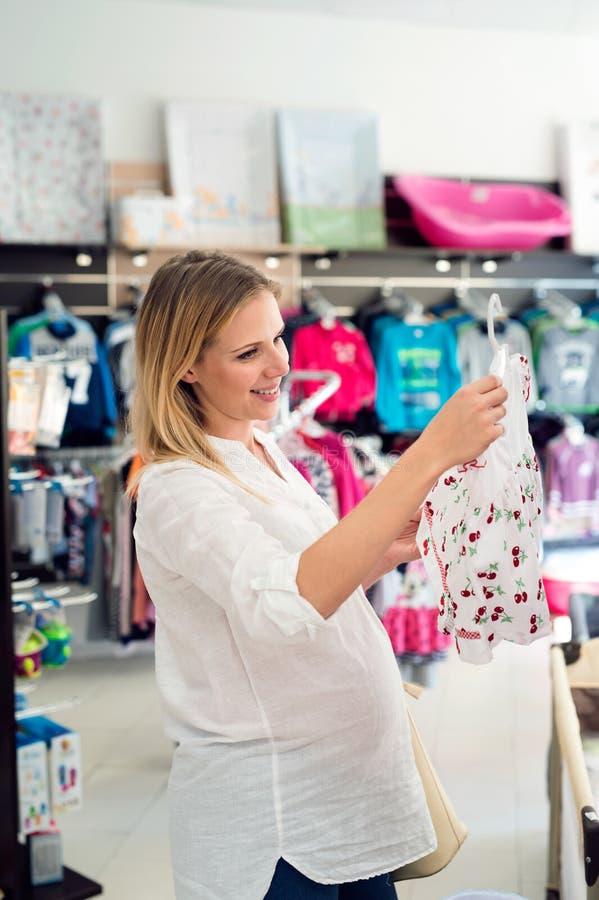 孕妇她的婴孩的购物衣裳 库存照片