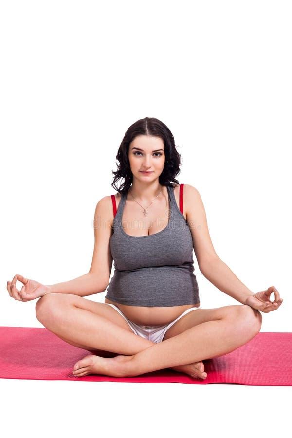 孕妇实践的瑜伽和思考 免版税库存图片