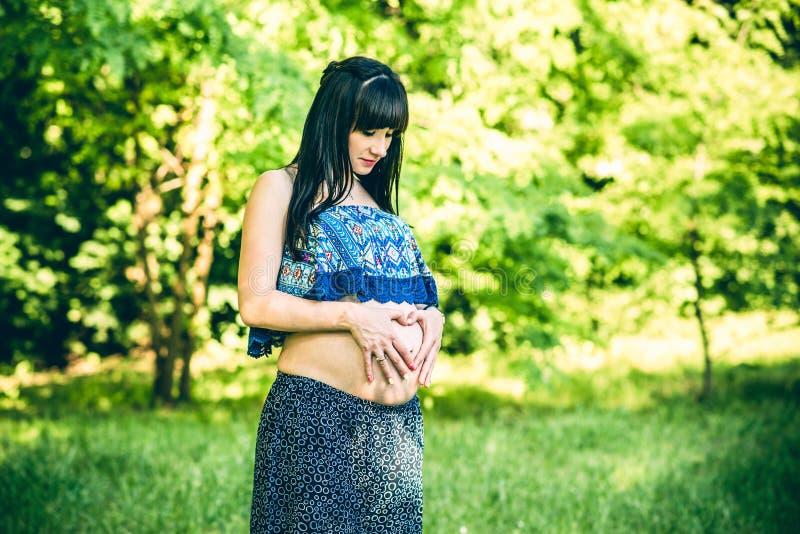孕妇室外用心形的手 免版税库存图片