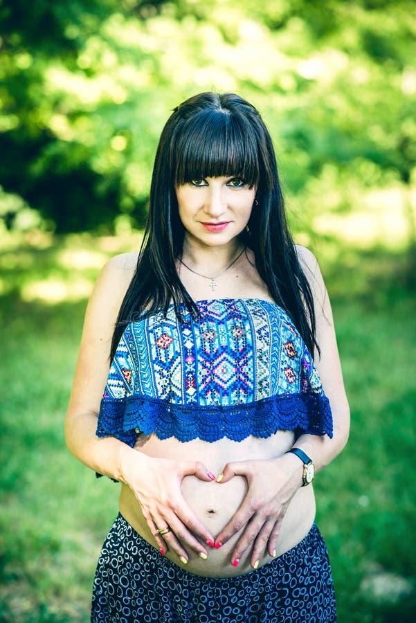 孕妇室外用心形的手 库存照片