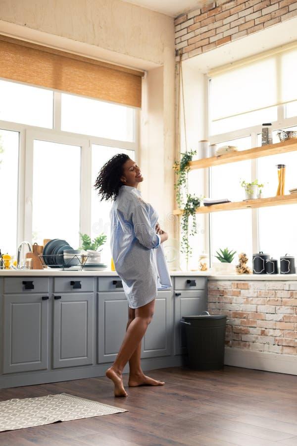 孕妇跳舞在她的厨房里早晨 免版税库存照片