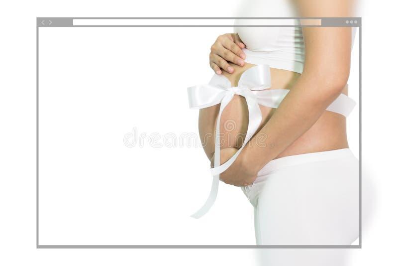 孕妇递握有白色丝带礼物的腹部在贝耳 免版税库存照片
