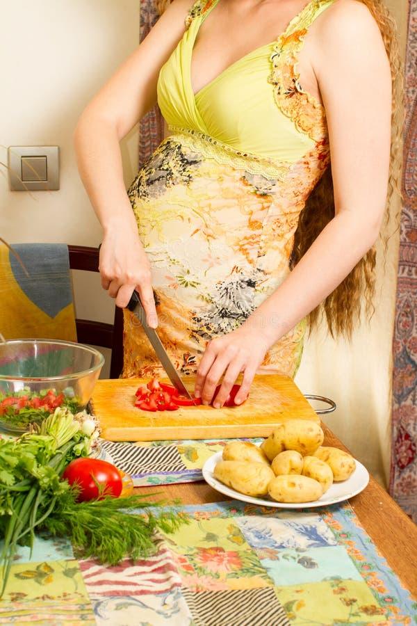 孕妇s手和腹部切口在厨房用健康食物 免版税图库摄影