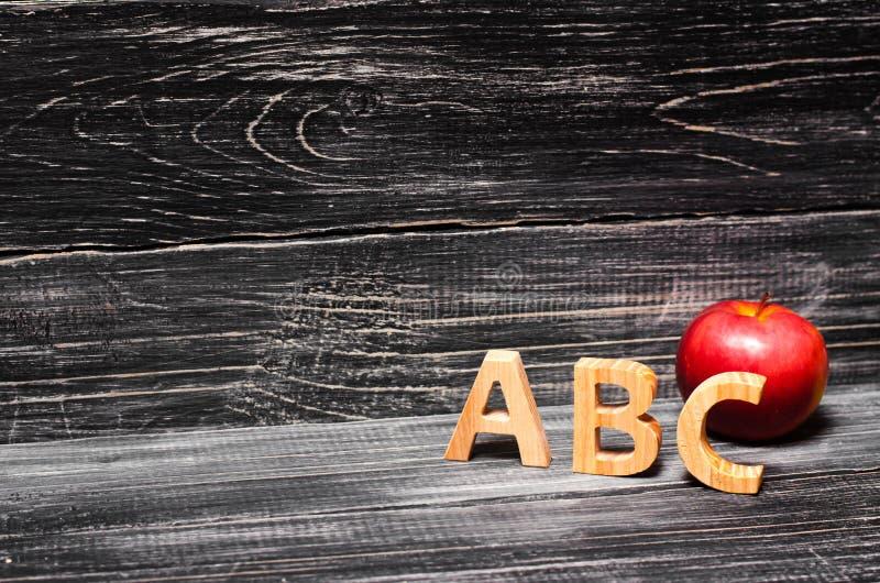 字母表信件和红色苹果在黑背景 concep 免版税库存照片