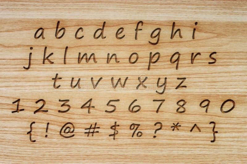 字母表和标点在木纹理背景 免版税库存照片