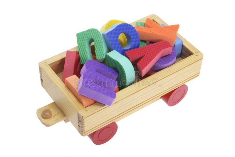 字母表木购物车的玩具 库存图片