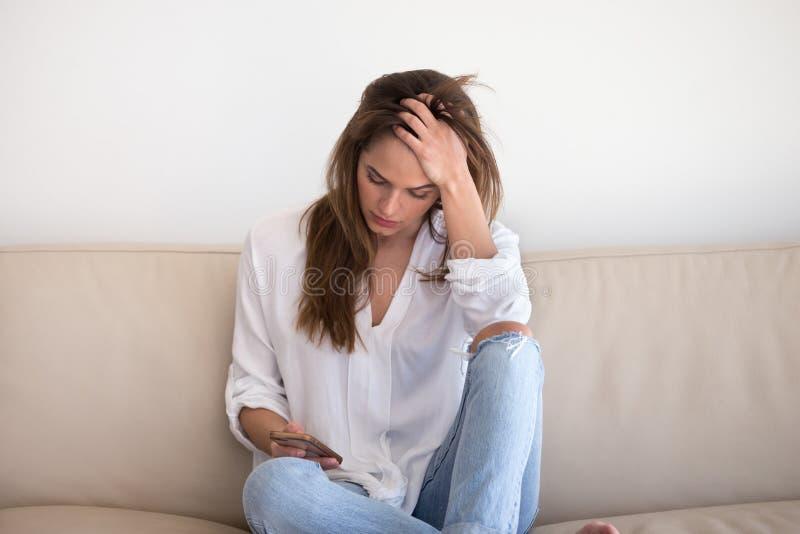 存从男朋友的哀伤的女孩智能手机等待的消息 免版税库存图片