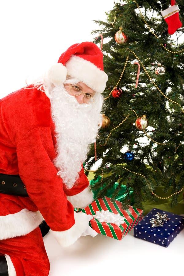 存在圣诞老人结构树下 免版税库存图片