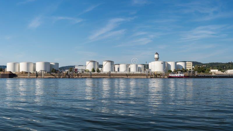 存贮筒仓、石油在河的河岸的燃料库和汽油在美丽的蓝天的德国西部与云彩 免版税图库摄影