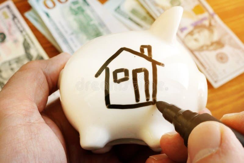 存金钱买议院 有家的存钱罐在边 免版税库存图片