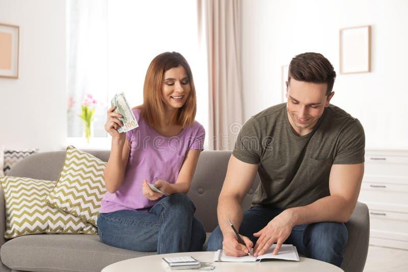 存金钱的夫妇处理的预算 图库摄影