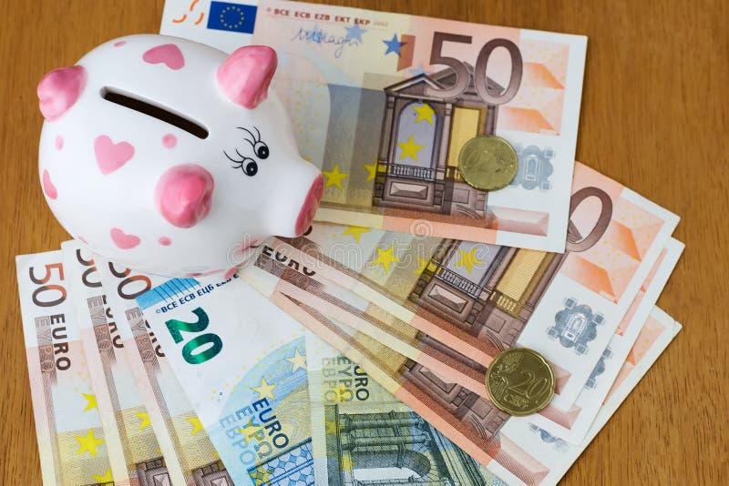 存钱罐和欧洲钞票在一张木桌上 财务 节省额 免版税图库摄影