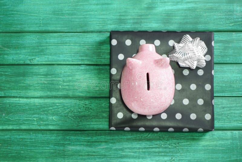 存钱罐和礼物盒在颜色木背景 攒钱的概念礼物的 库存图片