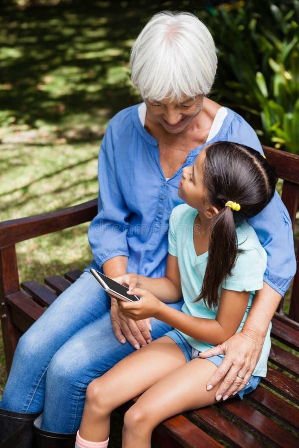孙女与看祖母的手机坐长木凳 免版税库存图片